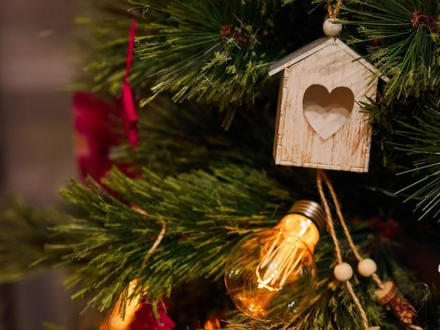 Giocattoli di natale del cuore di legno e torce elettriche sull'albero di natale