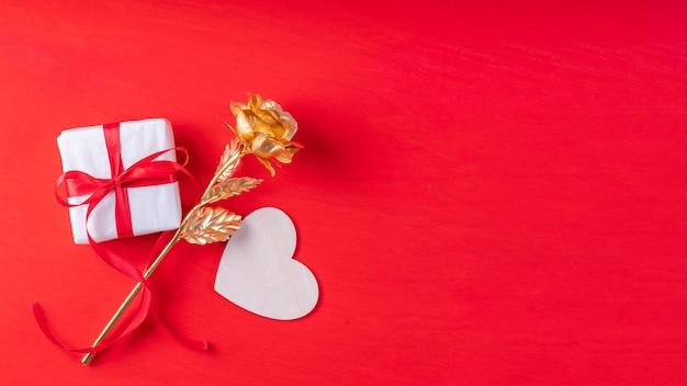 Forma di cuore in legno, un regalo in carta bianca e un nastro rosso e una rosa in oro giallo simbolo dell'amore