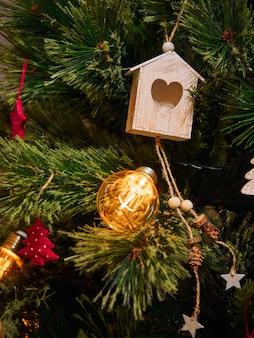 Giocattoli di legno del cuore e torce elettriche sull'albero di natale