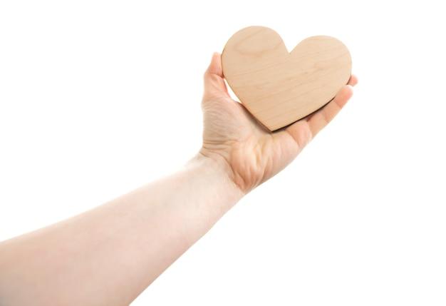 Il cuore di legno nella mano della donna contro il cielo bianco