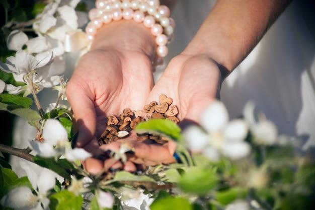 Cuori di legno amore alle mani della donna dietro di melo in fiore. concetto di pace e armonia. tenendo a forma di cuore amore simbolo vacanza san valentino romantico saluto stile di vita sentimenti concept
