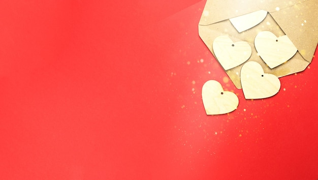I cuori di legno fuoriescono da una busta aperta su uno sfondo rosso.