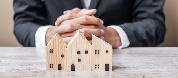 Modello di casa in legno sul tavolo da ufficio con il giovane uomo d'affari.
