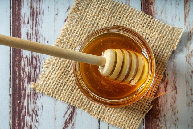 Bastone di miele in legno all'interno di un vasetto di miele puro di api su un vecchio tavolo rustico.