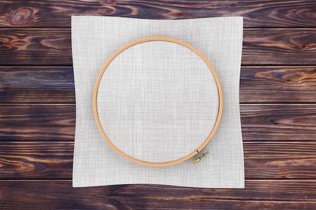 Cerchio in legno per punto croce. un telaio a tamburo per ricamo e tela con spazio libero per il tuo design su un tavolo di legno. rendering 3d