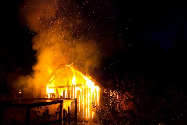 Casa in legno o fienile che brucia sul fuoco durante la notte.