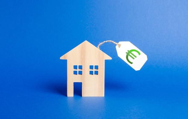 Figura della casa in legno e cartellino del prezzo in euro vendita di una casa o asta servizi di agenti immobiliari acquisto di immobili e investimenti liquidi e costosi