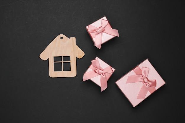 Statuetta di casa in legno e scatole regalo su sfondo nero. vista dall'alto