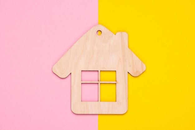 Statuetta di casa in legno o portachiavi su uno sfondo color pastello. vista dall'alto