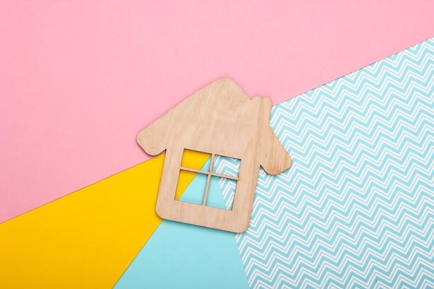 Statuetta di casa in legno su sfondo colorato pastello. vista dall'alto