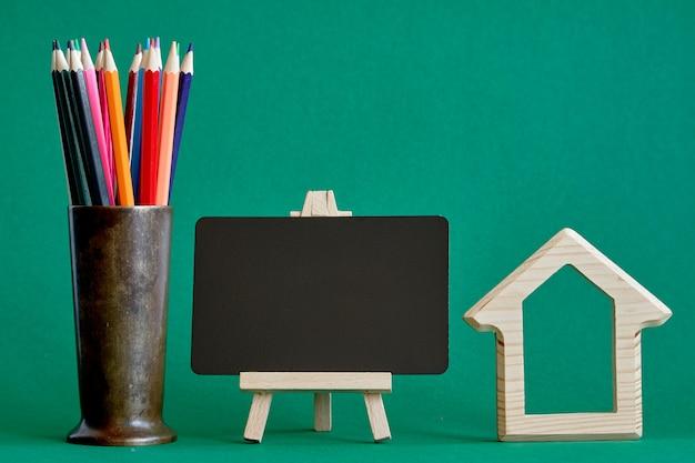 Statuina di casa in legno con lavagna in miniatura e matite multicolori