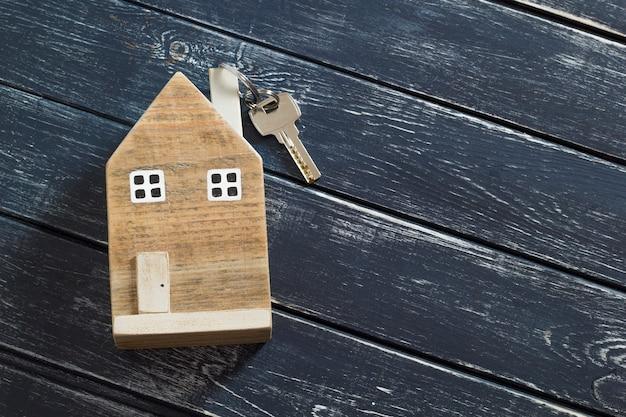 Casa in legno e chiave su uno sfondo scuro. copia spazio