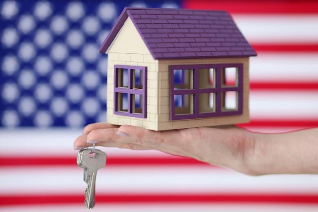 La casa e le chiavi di legno stanno trovandosi a disposizione davanti al primo piano della bandiera degli stati uniti
