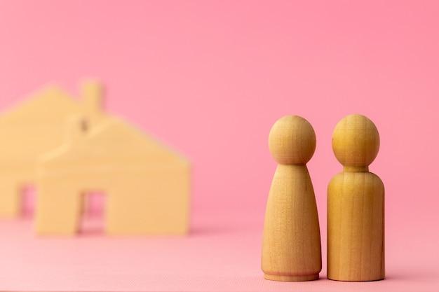 Miniatura di casa in legno e persone giocattolo su sfondo rosa