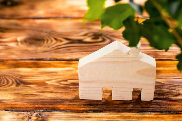 Miniatura della casa in legno sulla fine della superficie di legno sulla foto