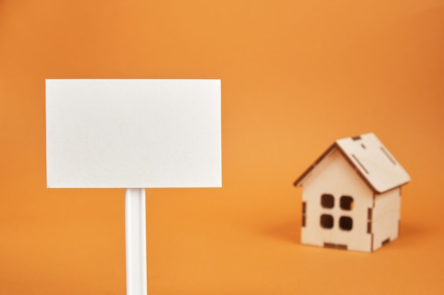 Modello di casa in legno e segno bianco su sfondo marrone copia spazio concetto di bene immobile