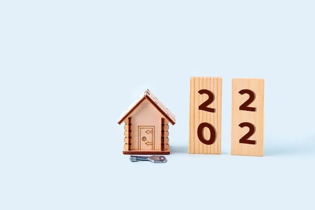 Modello di casa in legno, blocchi con numeri di iscrizione 2022 e chiave. concetto di acquisto e vendita di case e immobili nel nuovo anno. assicurazione casa, proprietà e mutuo.