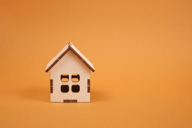 Modello di casa in legno su sfondo marrone copia spazio, concetto di bene immobile
