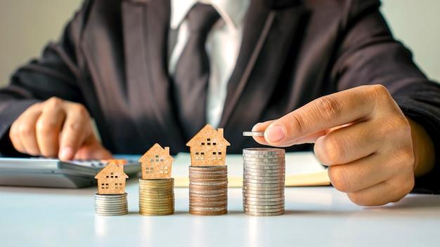 Modello di casa in legno su monete e mani di persone, idee di investimento immobiliare e transazioni finanziarie.