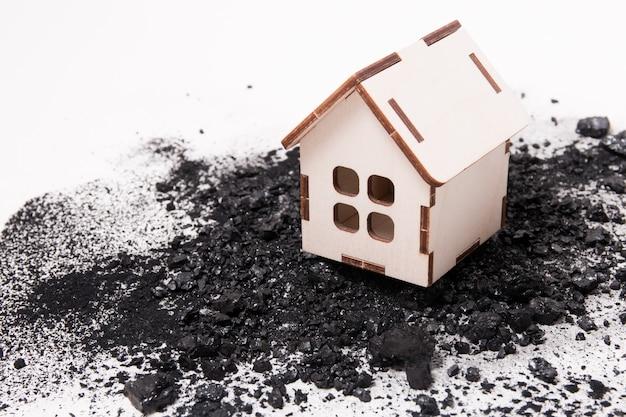 Modello di casa in legno su un mucchio di carbone