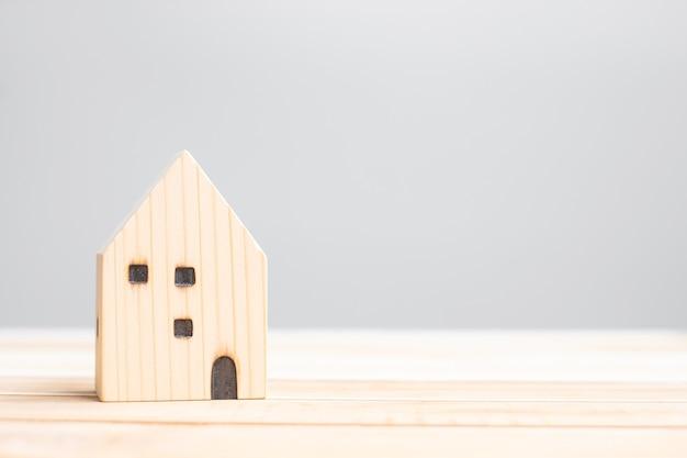 Modello di casa in legno sullo sfondo del tavolo. concetto di casa, crisi, recessione economica, senzatetto, immobiliare, acquisto o affitto e proprietà