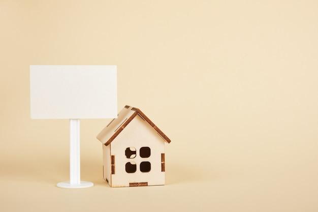 Modello di casa in legno e segno bianco bianco su sfondo beige copia spazio concetto di bene immobile