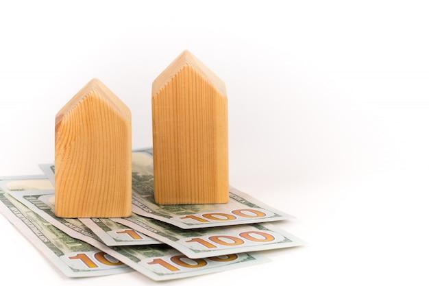 Modello di casa in legno con banconote in dollari, concetto di costo costoso della realtà
