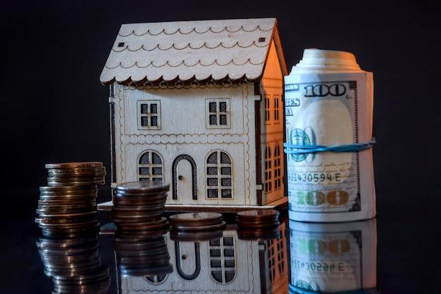 Modello di casa in legno con dollari in rotolo e monete