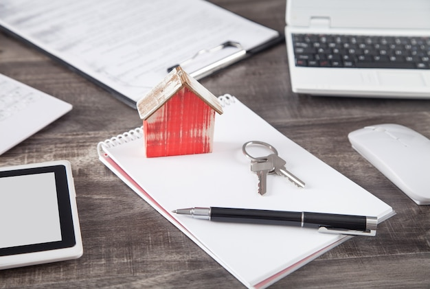 Modello di casa in legno con chiavi, penna e blocco note.