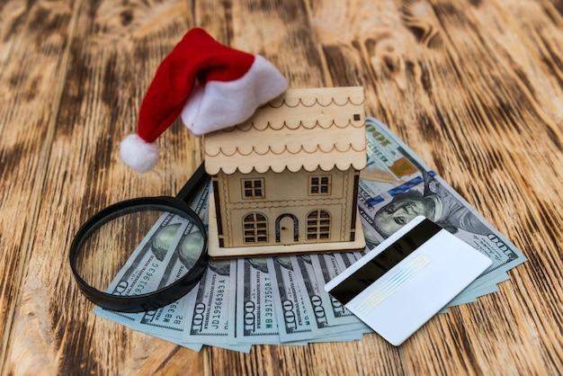 Modello di casa in legno con cappello santa e banconote in dollari