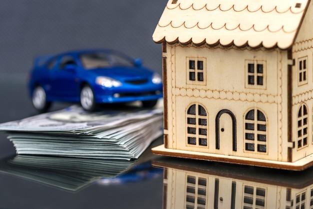 Modello di casa in legno con macchinina e mucchio di dollari