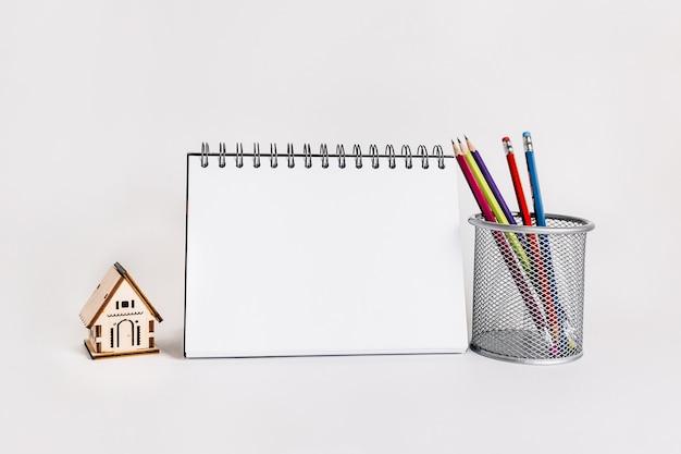 Casa in legno, blocco note e matita in superficie bianca