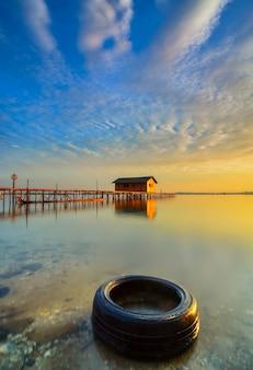 Casa in legno sul mare ad un bel tramonto