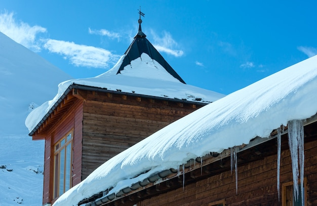 Casa in legno (con neve e ghiaccioli sul tetto) sul pendio di montagna invernale.