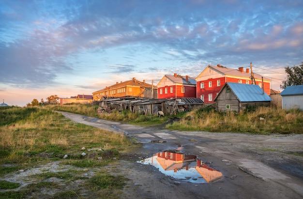 Case di legno del villaggio sulle isole solovetsky sotto i raggi del sole al tramonto