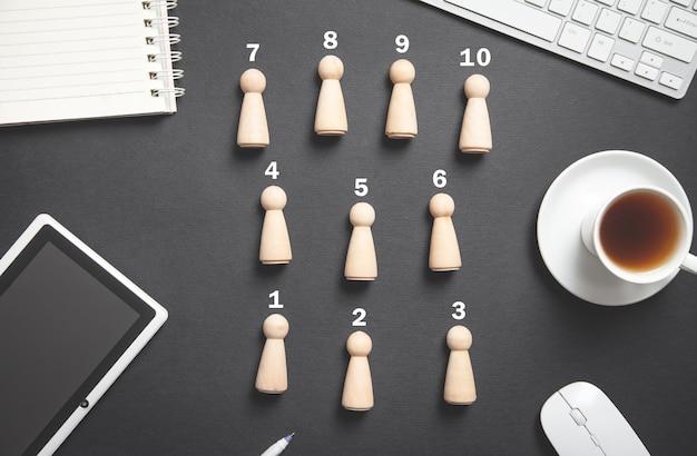 Figure umane in legno sulla scrivania da lavoro.