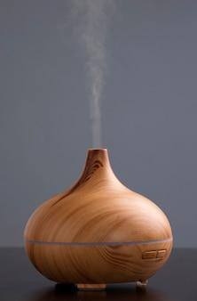 Umidificatore in legno sul tavolo con fumo di oli essenziali