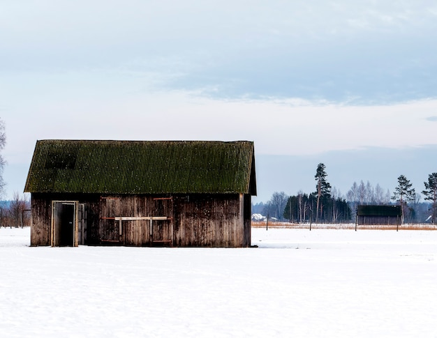 In inverno, una capanna di legno si trova al centro di un campo innevato.