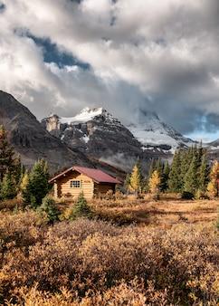 Capanne di legno con le montagne rocciose nella foresta di autunno al parco provinciale di assiniboine