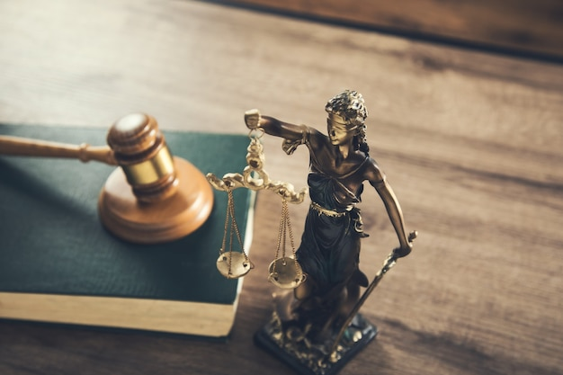Giudice di legno sul libro con la signora della giustizia sulla scrivania