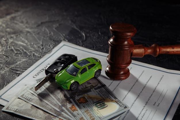 Martelletto del giudice in legno e macchinina verde con chiavi sui soldi. simbolo di diritto, giustizia e asta di automobili