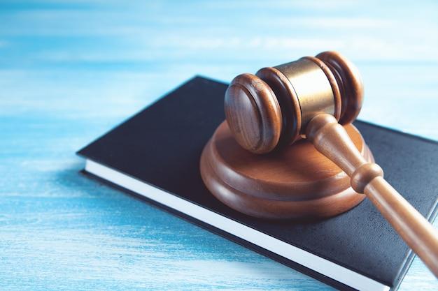 Martelletto del giudice in legno e libri di legge.