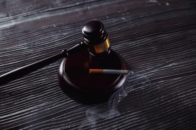 Martelletto del giudice in legno e sigaretta fumante in una stanza buia.