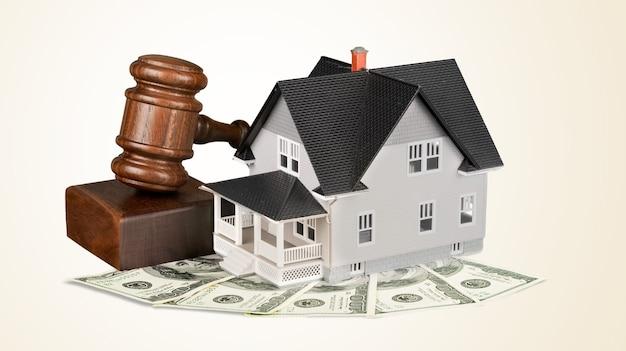 Martelletto giudice in legno e casa giocattolo sullo sfondo