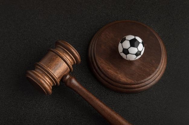 Martelletto del giudice in legno e pallone da calcio giocattolo. allenatore di calcio accusato. causa per commozione cerebrale.