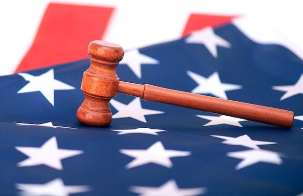 Martelletto in legno del giudice sulla bandiera degli stati uniti, immagine concettuale sulla corte