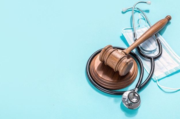 Martelletto in legno del giudice con mascherina medica e stetoscopio del medico su priorità bassa blu. legislazione sanitaria e concetto medico