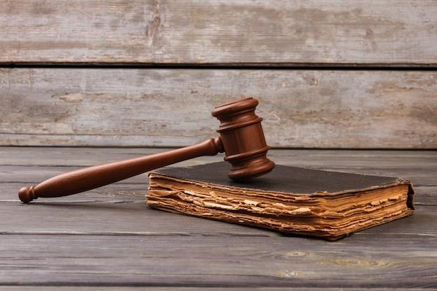 Martelletto dei giudici in legno e vecchio libro di legge. tavolo di legno grezzo in background.