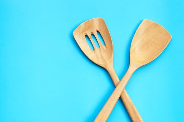 Spatola da cucina in legno sul tavolo blu.