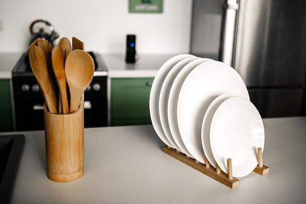 Utensili da cucina in legno in un bicchiere di legno sullo sfondo di una bella cucina moderna scaffale bianco con set di stoviglie